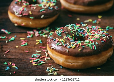 Pastries concept. Donuts with chocolate glaze with sprinkles, on wooden table blurry background.