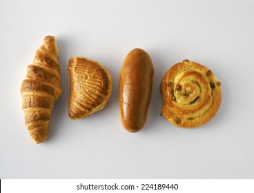 Pastries: croissant, apple turnover, bun, and raisin danish