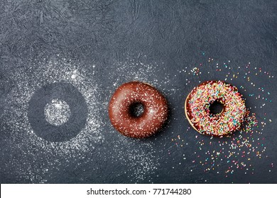 Pastry background. Chocolate donut or doughnut on black table top view. Flat lay. Copy space for text.