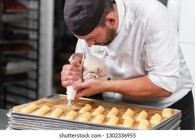 Pastry Chef with confectionary bag squeezing cream at pastry shop .