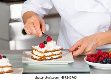 Un chef pastelero decorado con pastel de bayas