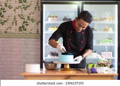 pastry chef decorating blue cake at indoors cafe and bakery store with refrigerator cake showcase behind as a background