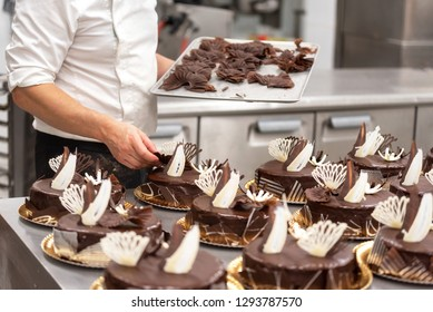 Pastry Chef decorating chocolate cakes in the kitchen of pastry shop .