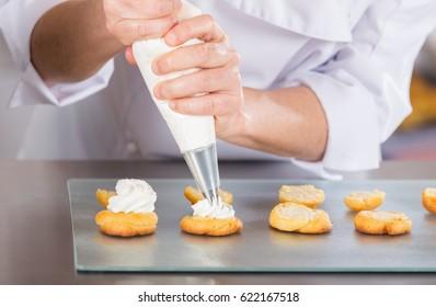 Chef pastelero que acaba unos deliciosos profiteroles crema