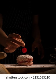 Pastry chef in the kitchen decorating a cake of fruit