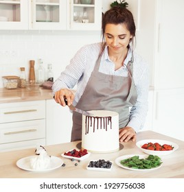 Pastry chef in the kitchen decorating a cake of chocolate