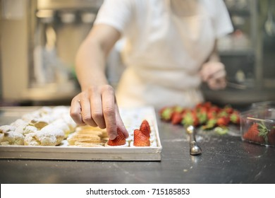Pastry chef making pastries with cream and fruits