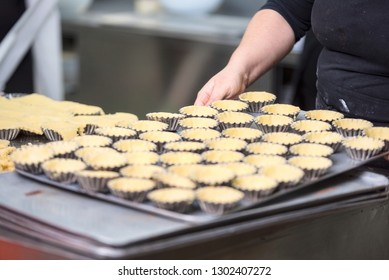 Pastry chef making tartlets, putting the dough in baking dishes, at kitchen of pastry shop .