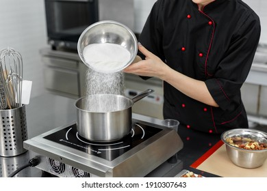 Pastry chef pours the sugar into a saucepan.