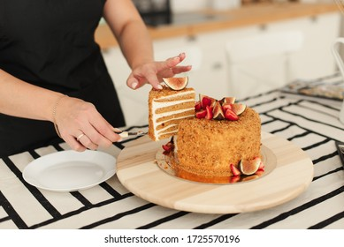 The pastry chef at work. Honey cake. Cake with figs. Cut the cake. Piece of cake. Honey confectionery.
