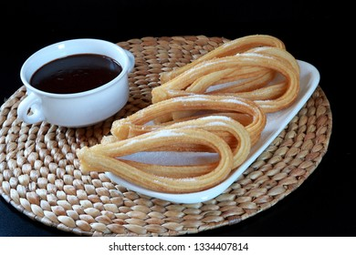 Pastry (Churros) sprinkled with sugar and Chocolate
