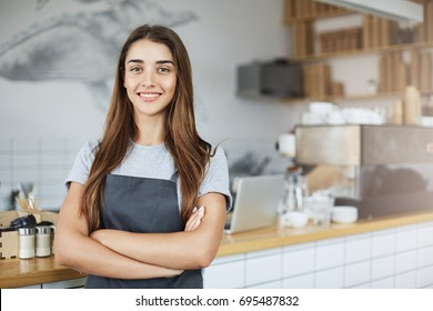 Pastry and coffee shop owner looking confident smiling at camera with arms crossed. Positive business concept.