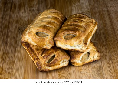 Pastry sausage rolls on a wooden table top