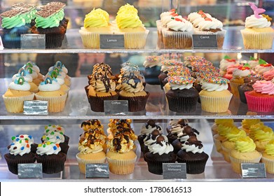 Pastry shop display window of delicatessen bakery store with variety of cupcakes.