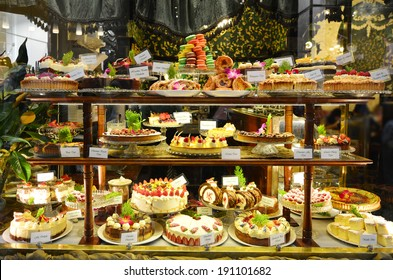 Pastry shop display window of delicatessen store with variety of cakes.