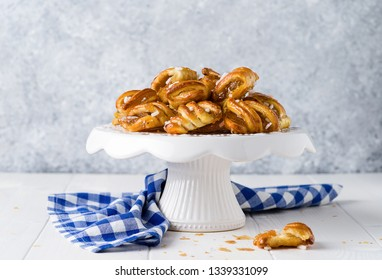 Pastry strudels with apricot jam on wooden background.