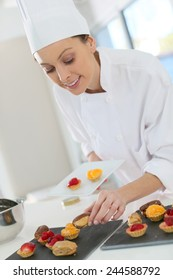 Pastry-cook preparing plate of cake bites