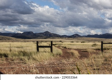 Pasture gateway, road tracks and dry grassland with hills on cloudy day in Autumn/Hills and Grassland with Pasture Entrance and Dirt Road on Cloudy Blue Sky Autumn Day/Ranch gate and Fall landscape