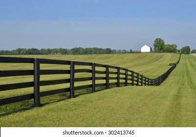 Pastures in the countryside landscape with a dark brown painted country style fence on a sunny summer day
