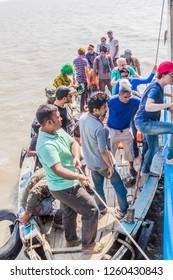 PASUR, BANGLADESH - NOVEMBER 14, 2016: Tourists leaving a boat and boarding their ship during their Sundarbans tour, Bangladesh.