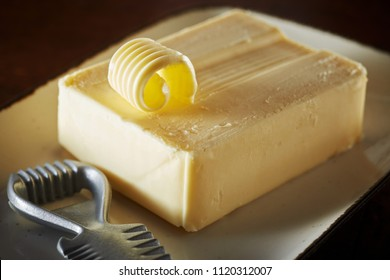 Pat of farm fresh butter with metal curler on a plate and a partially formed curl of butter on the top of the block in a close up view
