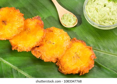 Patacon fried pieces of crushed green banana. Guacamole. On the wooden table (toston, tachino)