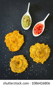 Patacon or toston, fried and flattened pieces of green plantains, a traditional snack or accompaniment in the Caribbean, guacamole, photographed overhead on slate with natural light