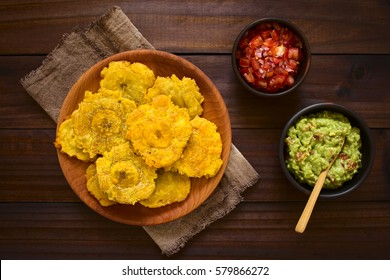 Patacon or toston fried and flattened pieces of green plantain, traditional snack or accompaniment in the Caribbean, guacamole and tomato onion salad beside, photographed overhead with natural light