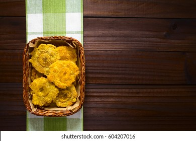 Patacon or toston, fried and flattened pieces of green plantains, a traditional snack or accompaniment in the Caribbean, photographed overhead on dark wood with natural light