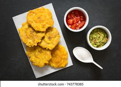 Patacon or toston, fried and flattened pieces of green plantains, traditional snack or accompaniment in the Caribbean, guacamole, tomato and onion salad, salt on side, photographed with natural light