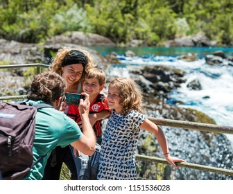 PATAGONIA, CHILE - JANUARY 4, 2018: The family is photographed against the background of a waterfall in national park Vicente Perez Rosales