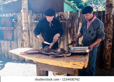 PATAGONIA, CHILE-NOV. 14, 2012:   A Chilean gaucho and his assistant demonstrate the carving of a whole barbecued lamb outdoors at a ranch in Patagonia.