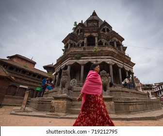 Patan, Nepal - Circa September 2017 - A worm's eye view of an unidentified woman walking in front of the  Krishna Temple located in Patan Durbar Square, Nepal
