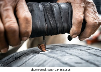 Patch a tyre,Hands of old man patching puncture tubeless car tire,repair rubber surface that have been stabbed by nails,recap on the tire tread,stabbing rubber patch needle and glue into the puncture