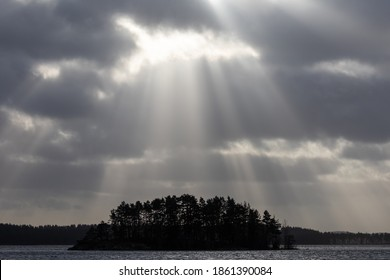 Patches of sunlight shining through clouds with an island on a lake below