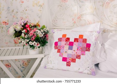 patchwork quilt pillow with heart from squares in cotton near flower vase as a décor of bedroom