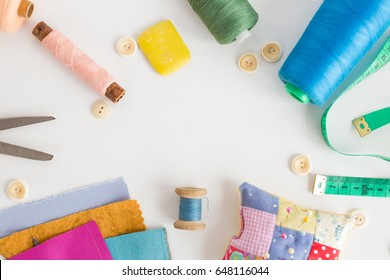 patchwork, sewing concept - close-up on white desk with colorful skeins of thread, measuring meter, buttons, scissors, pincushion, equipment for needlework. Space for the text.