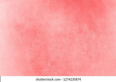 Patchy and  grungy fibrous paper background texture with coral hues fading towards white.