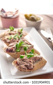 Pate spread on bread slices with greens and condiments. Chicken liver pate spread.