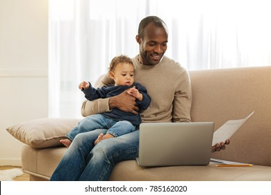 Paternal leave. Cheerful dark-eyed bearded afro-american man smiling and holding his son on his lap while working on the laptop and holding a sheet of paper