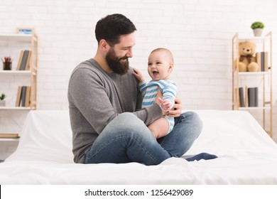 Paternal pride. Daddy and his cute baby boy laughing together on bed, copy space