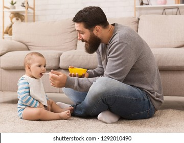 Paternity leave. Father feeding his hungry baby son, sitting on floor at home, copy space