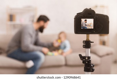 Paternity leave is interesting. Father recording educational video about how to feed hungry baby with porridge, focus on camera