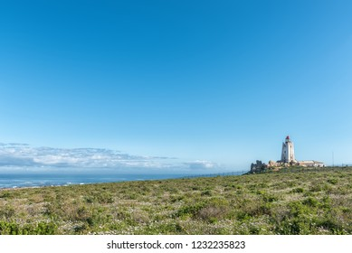 PATERNOSTER, SOUTH AFRICA, AUGUST 21, 2018: The Cape Columbine Lighthouse in the Cape Columbine Nature Reserve near Paternoster. Wild flowers are visible