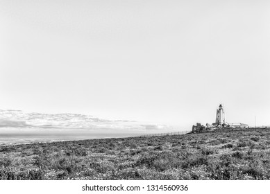 PATERNOSTER, SOUTH AFRICA, AUGUST 21, 2018: The Cape Columbine Lighthouse in the Cape Columbine Nature Reserve near Paternoster. Wild flowers are visible. Monochrome
