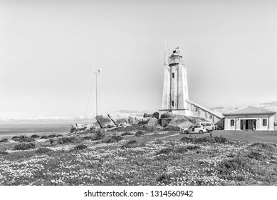 PATERNOSTER, SOUTH AFRICA, AUGUST 21, 2018: The Cape Columbine Lighthouse in the Cape Columbine Nature Reserve near Paternoster. Wild flowers and vehicles are visible. Monochrome