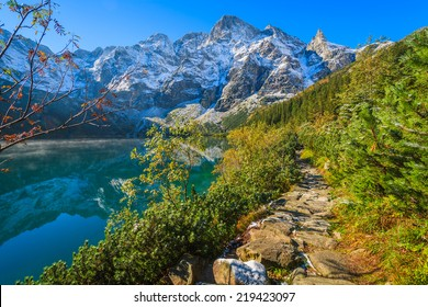 Path along Morskie Oko lake in autumn colours with fresh snow covered peaks, High Tatra Mountains, Poland