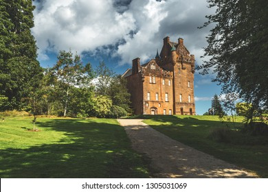 Path to the ancient castle. Northern Ireland. Picturesque scene the vintage building surrounded by the green lawn and trees. Blue cloudy sky background. Stunning Irish landscape. Historical house.