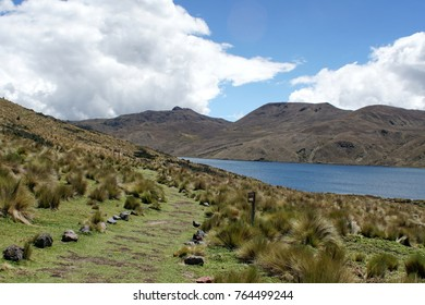 Path beside a highland lake with mountains behind it at Antisana Ecological Reserve, Ecuador
