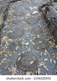 Path covered by gravel and dry leaves, with tops of tree trunks marking the steps and flanked by small wooden stumps